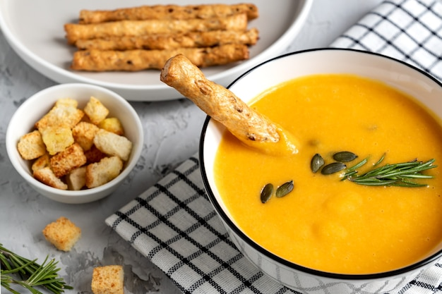 Kürbis-karotten-suppe mit sahne, kürbiskernen, croutons und grossini-brotstangen auf dar k holzhintergrund. rustikaler stil, selektiver fokus.