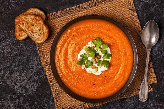 Kürbis-karotten-suppe mit sahne, samen und petersilie