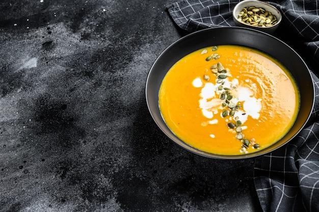 Kürbis-karotten-suppe mit sahne und gewürzen. schwarzer hintergrund. draufsicht. speicherplatz kopieren