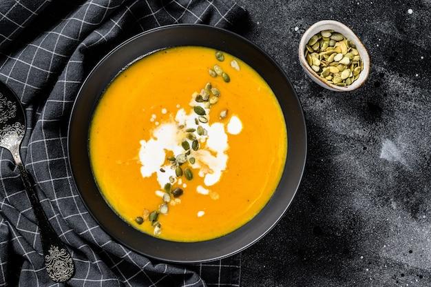 Kürbis-karotten-suppe mit sahne und gewürzen. schwarzer hintergrund. draufsicht