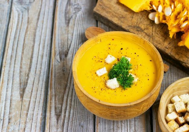 Kürbis-karotten-suppe, tadka mit sahne und petersilie auf dunklem holztisch. draufsicht.