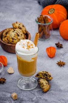 Kürbis latte in einem glas mit würziger creme und einer zimtstange auf einer grauen steinoberfläche mit plätzchen mit schokoladensplittern