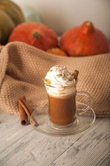 Kürbis latte in einer transparenten tasse nahaufnahme und kopieren raum latte mit creme zimt kürbisse kürbiskerne auf einem weißen teller latte und pullover