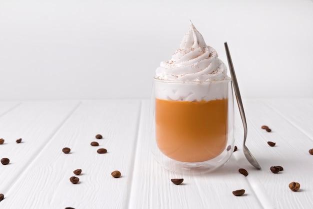 Kürbis latte mit schlagsahne und gewürzen auf weißem holztisch