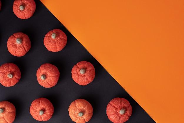 Kürbis-marshmallow-muster auf schwarz mit orangefarbenem hintergrund, süße leckerei für halloween, kopierraum.