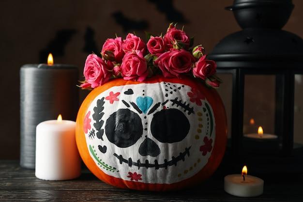 Kürbis mit catrina-schädel-make-up und halloween-accessoires