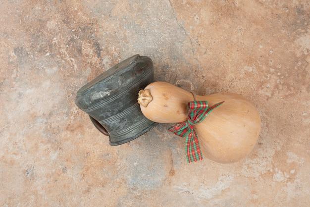 Kürbis mit schleife und altem kessel auf marmor.