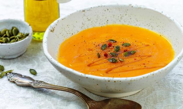 Kürbis-möhren-püree-suppe mit samen, rosa pfeffer und olivenöl
