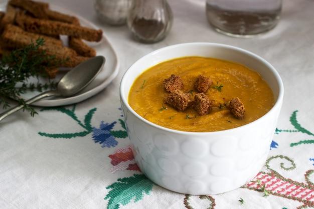 Kürbis- oder karottencremesuppe mit croutons und thymian auf holz