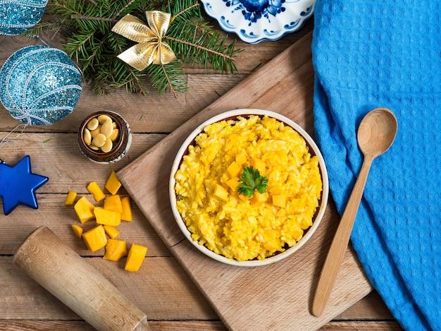 Kürbis-reis-porridge mit weihnachtsdekoration in blau- und goldfarben