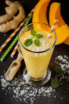 Kürbis-smoothies mit ingwer- und kokosnussspänen und minze in einem glas auf einer dunklen betonoberfläche. gesundes und leckeres getränk zum frühstück