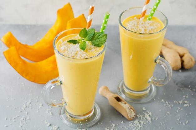Kürbis-smoothies mit ingwer- und kokosnussspänen und minze in einem glas auf hellem stein oder betonoberfläche