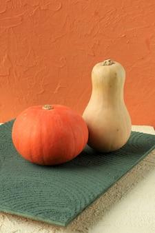 Kürbis und butternut-kürbis auf buntem hintergrund, konzept halloween