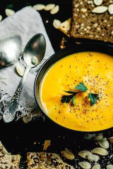 Kürbis- und karottensuppe mit sahne und kürbiskernen