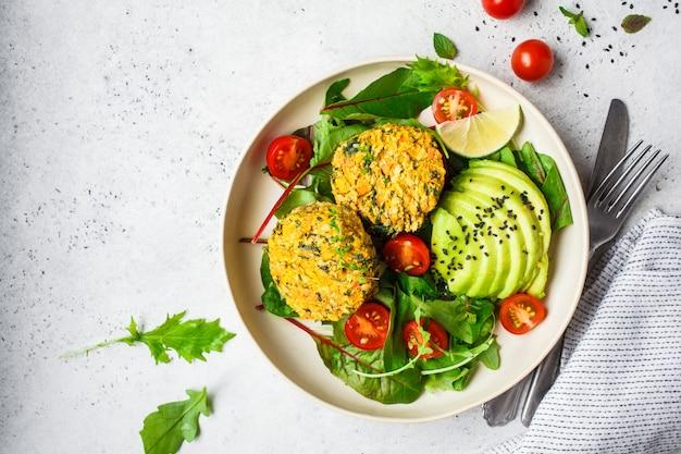 Kürbis- und quinoakoteletts des strengen vegetariers mit salat in einer weißen platte, draufsicht.