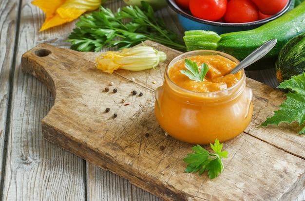 Kürbis-zucchini-paste in einem glas umgeben von den zutaten