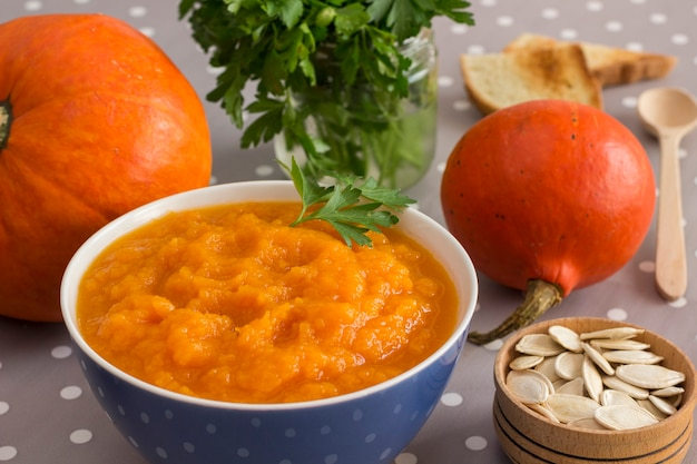 Kürbisbrei in einer schüssel zwischen orangenkürbissen und samen