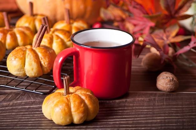 Kürbisbrötchen auf dem backblech und einer tasse tee. herbstkonzept. warm und gemütlich.