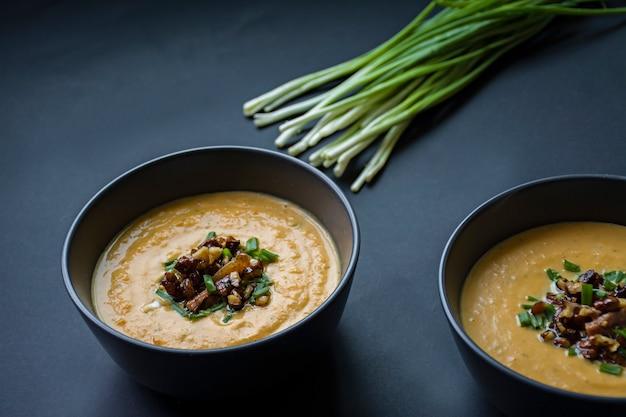 Kürbiscremesuppe mit kräutern und nüssen, serviert in einer dunklen schüssel. richtiges und gesundes essen. vegetarisches gericht.