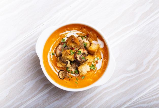 Kürbiscremesuppenpüree mit pilzen, croutons und sahne in weißer keramikschale auf weißem rustikalem holzhintergrund, draufsicht, nahaufnahme. köstliche traditionelle suppe, hausmannskost