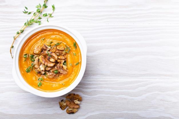 Kürbiscremesuppenpüree mit walnüssen, olivenöl und kräutern in weißer keramikschale auf weißem rustikalem holzhintergrund, draufsicht, nahaufnahme. leckere vegane suppe, platz für text