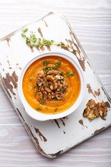 Kürbiscremesuppenpüree mit walnüssen, olivenöl und kräutern in weißer keramikschale auf weißem rustikalem holzhintergrund, draufsicht, nahaufnahme. leckere vegane suppe