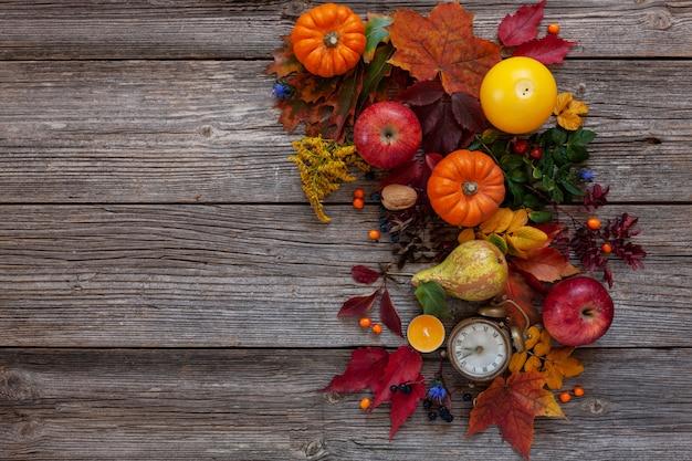 Kürbise, äpfel, birnen, borduhren und kerzenhintergrund