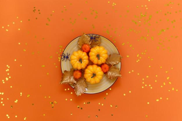 Kürbise auf einem gelben teller mit spinnen auf orange mit goldenen konfettis.