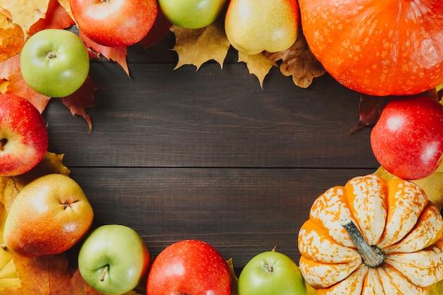 Kürbise mit bunten ahornblättern, reifen äpfeln und birne auf dunklem hölzernem hintergrund
