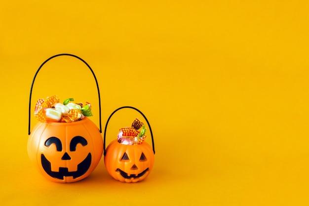 Kürbiseimer mit süßigkeiten und spinnen auf einem orange hintergrund