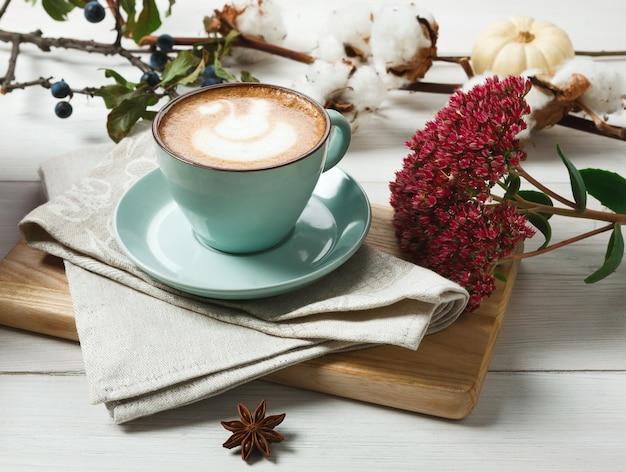 Kürbisgewürz latte. blaue kaffeetasse mit cremigem schaum auf dem schreibtisch, getrockneten herbstblumen, schlehe und kleinen gelben kürbissen. heiße getränke im herbst, saisonales angebotskonzept