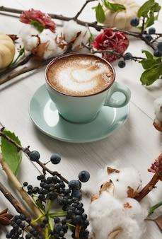 Kürbisgewürz latte. blaue kaffeetasse mit cremigem schaum, getrockneten herbstblumen, schlehe und kleinen gelben kürbissen. heiße getränke im herbst, saisonales angebotskonzept