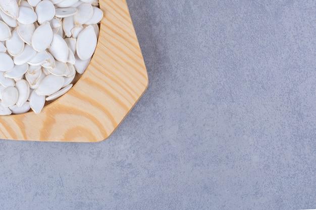 Kürbiskerne in einem holzteller, auf dem marmor.