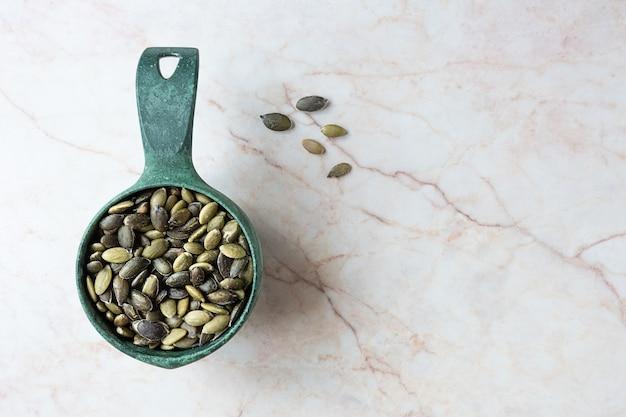 Kürbiskerne in einer kugel auf marmorhintergrund