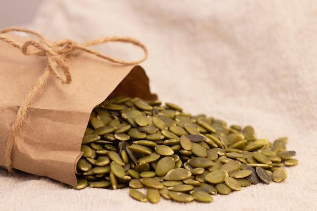 Kürbiskerne in einer papiertüte auf natürlichem leinen. kürbiskern vitamine der gruppe b und magnesium.