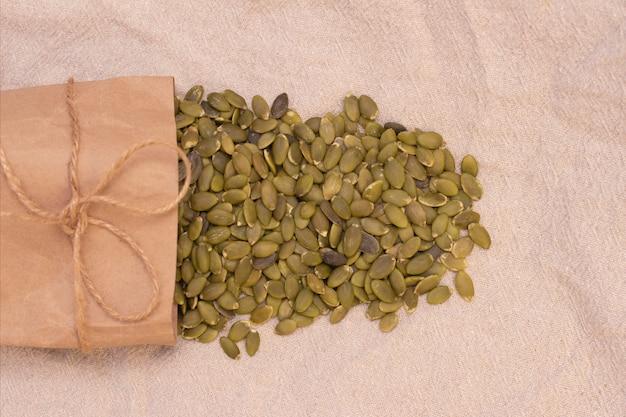 Kürbiskerne in einer papiertüte auf natürlichem leinen. kürbiskernvitamine der gruppe b