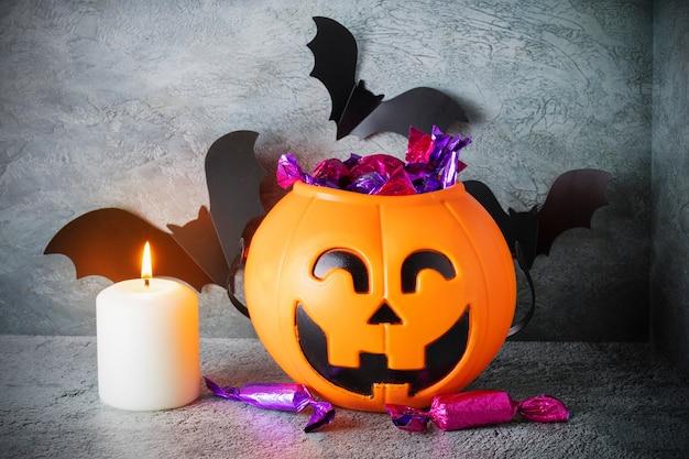 Kürbiskorb mit gesicht der jack-laterne mit süßigkeiten, brennender kerze, papierfledermäuse auf grauem hintergrund
