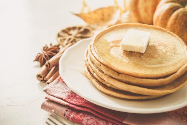 Kürbispfannkuchen auf weißer platte mit butter und honig