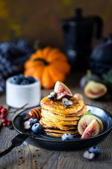 Kürbispfannkuchen mit sirup oder honig, leinsamen, feigen, blaubeeren in einem dunklen teller auf dem tisch, selektiver fokus, kopierraum