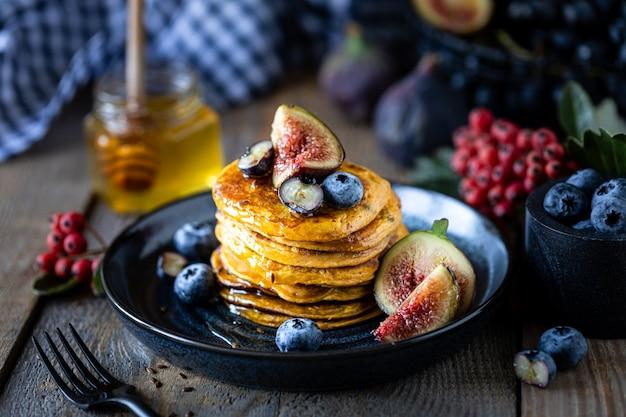 Kürbispfannkuchen mit sirup oder honig, leinsamen, feigen, blaubeeren in einem dunklen teller auf dem tisch