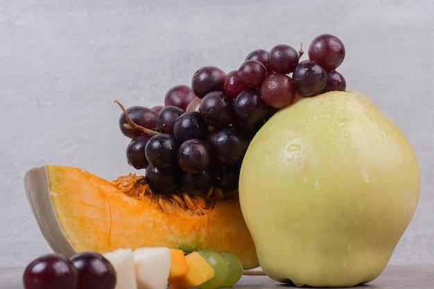 Kürbisscheibe mit birne und trauben auf weißem tisch.