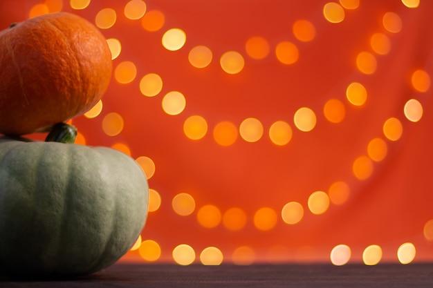 Kürbisse auf orangem hintergrund mit bokeh. halloween. platz kopieren.