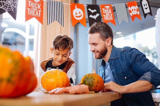 Kürbisse für halloween. vater und sohn sitzen am tisch im wohnzimmer, während sie kürbisse für halloween schnitzen