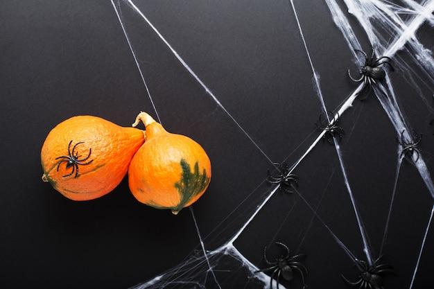 Kürbisse mit spinnen und spinnennetz auf schwarzer oberfläche. halloween feiertagsdekorationen. flach liegen
