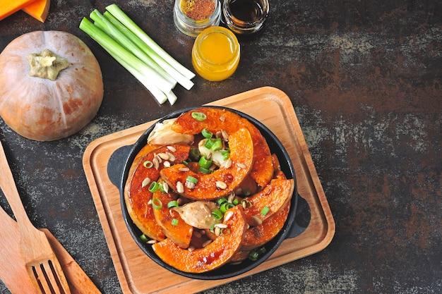 Kürbisstücke in einer kleinen pfanne mit gemüse und samen gebacken. gebackener kürbis. veganes mittagessen mit würzig gebackenem kürbis. nützlicher herbstsnack. halloween-mittagessen.