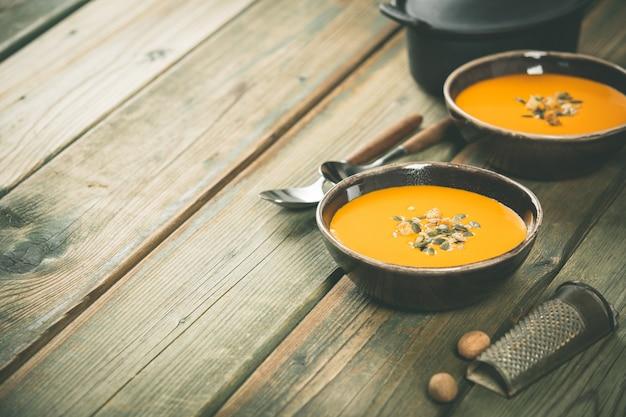 Kürbissuppe auf holztisch, gemütliches lebensmittelkonzept