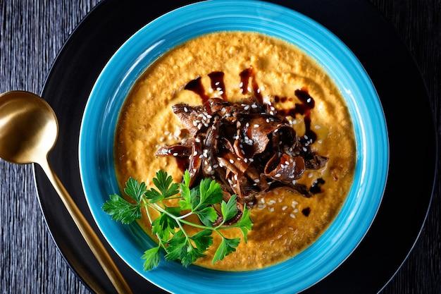 Kürbissuppe aus geröstetem kürbispüree und waldpilzbrühe, belegt mit sesam, veganes komfortgericht, serviert auf blauem teller mit löffel und knoblauch auf dunklem holzhintergrund, draufsicht