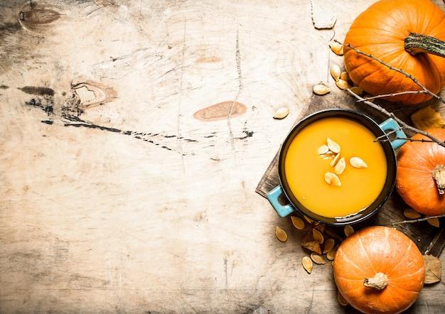 Kürbissuppe. gekochte suppe von einem reifen kürbis auf holztisch.
