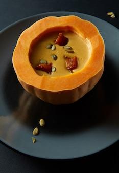 Kürbissuppe in einem kürbis im schwarzen tisch