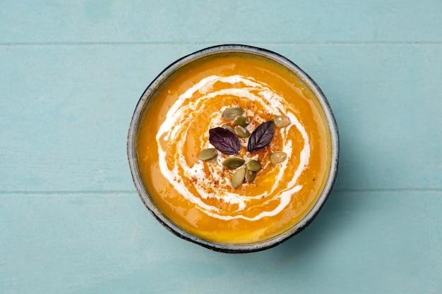Kürbissuppe in einer schüssel auf einem blauen hölzernen hintergrund.